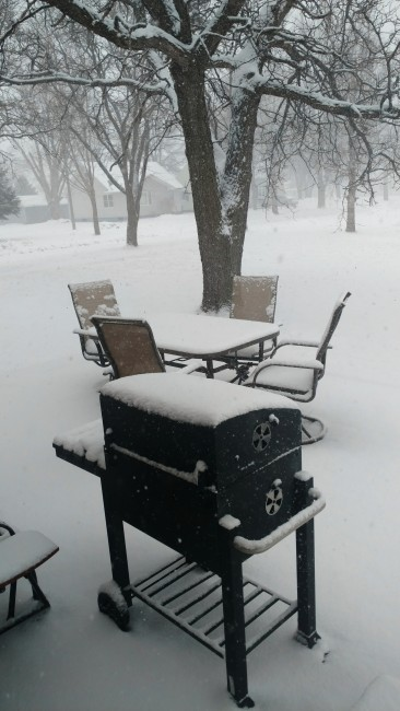 Patio furniture and the grill covered in swow
